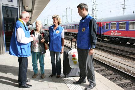"""Umsteigehilfe bei der Bahnhofsmission – Söder und Wöhrl beteiligen sich an Aktion """"Rollentausch""""."""