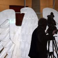 Ein Kameramann auf der Pressetribüne. Im Hintergrund der Bundestagsadler. Medien, Presse, Kamera, Stativ, Adler. © DBT/Hans-Günther Oed